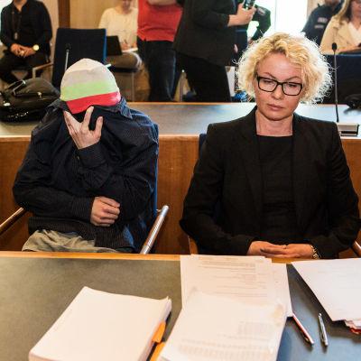 Puolustuksen asianajaja Minna Pilviö Tampereen Oikeustalon tiloissa salissa 15. Vieressä vasemmalla murhasta epäilty henkilö. Taustalla murhan tilauksesta epäillyn asianajaja.