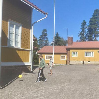 Två skolelever med munskydd spelar fotboll på gårdsplan.