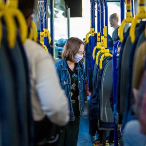 Nainen käytti kasvomaskia bussissa ensimmäisenä suosituspäivänä 14. elokuuta.
