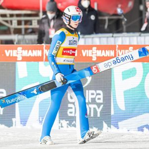 Halvor Egner Granerud går med skidorna i händerna.