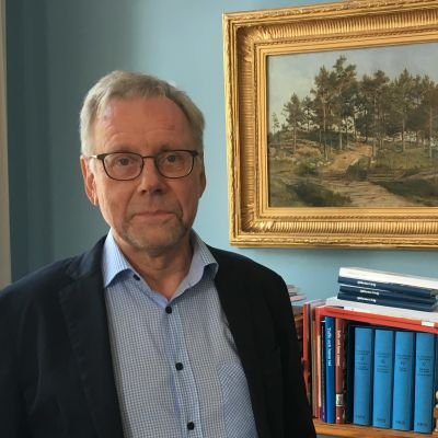 Mikko Hupa står i sitt arbetsrum framför en tavla och en liten bokhylla.