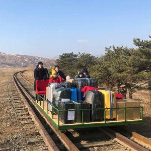 En järnvägstralla lastad med kappsäckar och barn skuffas framåt av en man och en kvinna.