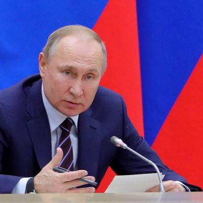 Vladimir Putin sitter bakom ett bord och håller tal.