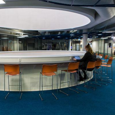 Opiskelija opiskelee yksin etänä tyhjän pöydän ääressä.