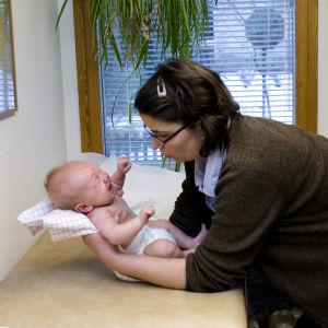 Terveydenhoitaja tai sairaanhoitaja tutkii vauvaa