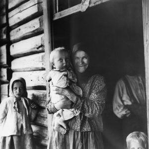 I. K. Inhan valokuvassa isoäiti ja perheen lapsia talon ovella