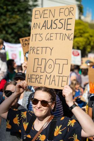 """En klimatdemonstrant i London med ett plakat med texten """"Even for an aussie it's getting pretty hot here mate""""."""