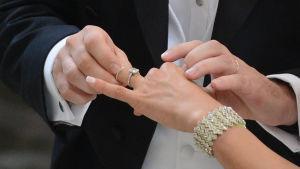 Brud får ring på sitt finger vid altaret.