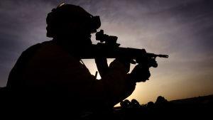 Konturerna av en beväpnad, hjälmbeklädd soldat i solnedgång i Afghanistan.