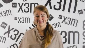 Sofia Syrjänen står mot en vägg.