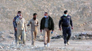 Irakiska poliser inspekterar en massgrav i Hammam Al-Aili, söder om Mosul.