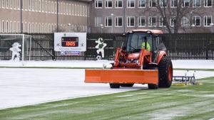 En traktor som kör på en snöig fotbollsplan