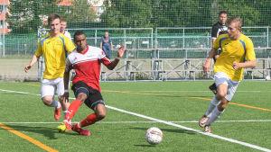 Tre fotbollsspelare följer bollens gång på planen