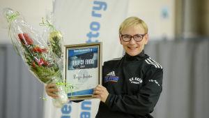 Raija Jurkko poserar med diplom och blommor.