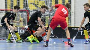 EN spelare skjuter bollen och en annan försöker stoppa skottet.