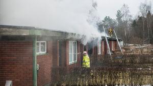 Brandmän vid det brinnande huset.