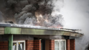 Kraftig, mörk rök stiger från radhusets tak.