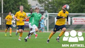 Fotbollsspelare springer efter en boll. De flesta är klädda i gult och svart och några i grön och vitt. Bollen är rakt framför ansiktet på en av de gul-svarta spelarna.