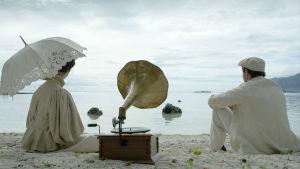 mies ja nainen istuvat hiekkarannalla gramofonin kanssa.