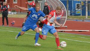 Teemu Lammi och en HJS-spelare springer efter bollen.