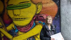 En kvinna står framför en väggmålning.