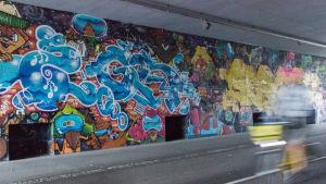 En väggmålning under en bro längs en cykelväg.