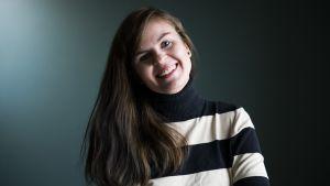 Ung glad kvinna med långt mörkblont hår och blåvitrandig polotröja mot grönblå vägg