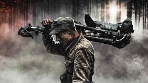 Sotilas kantaa konekivääriä savuisessa metsässä.