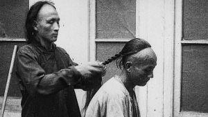 Mies letittää toisen hiuksia.