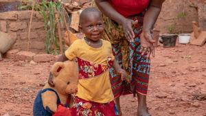 Tyttölapsi leikkii iloisena nallekarhun kanssa