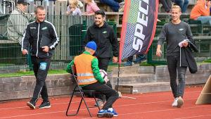 Tre män går på en sportplan och ser nöjda ut. En man sitter på en stol med ryggen till. Publik i bakgrunden.