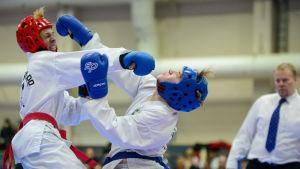 Två idrottare slår varandra i en match i taekwondo.