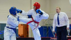 Ignatiev (röd hjälm) och Ekblad i en taekwondomatch. Teppo Häyrynen dömer