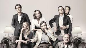 Neljä naista ja kolme miestä istuvat sohvalla ja seisovat sohvan takana, katsovat kameraan, osa hymyilee.