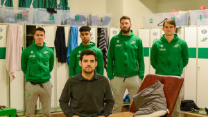 Fyra spelare och en tränare i ett omklädningsrum.