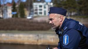Poliisimies nojaa sillan kaiteeseen ja miettii.