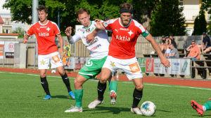 HIFK:s Hannu Patronen har bollen och skuggas av EIF:s Zacharias Ekström.