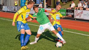 Zacharias Ekström kämpar om bollen mot två Gnistanspelare.