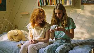 Två flickor sitter på en säng på 1980-talet.