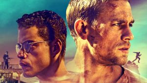Elokuvan graafinen markkinointikuva. Turkoosilla taustalla päänäyttelijöiden Charlie Hunnam ja Rami Malek päät katsovat eri suuntiin.