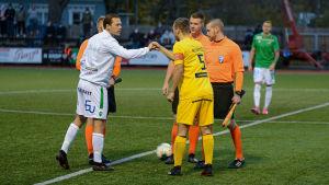 Lagkaptenerna Zacharias Ekström (EIF) och Lassi Nurmos (AC Oulu) hälsar på varandra före matchen. På bilden ses också domaren Joni Hyytiä.