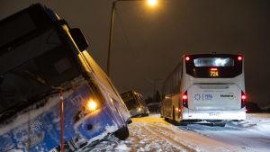En buss ligger på sned i snödrivan invid en väg.