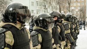 Poliser står på en rad utomhus i Moskva.