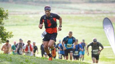 En löpare kommer upp för en backe.