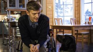 En svart labrador sitter bredvid en man i rullstol. De ser varandra i ögonen.