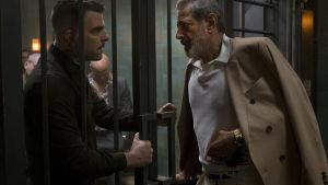 Jeff Goldblum och Zachary Quinto i rollen som skurkar står på varsin sida om en gallerförsedd grind.