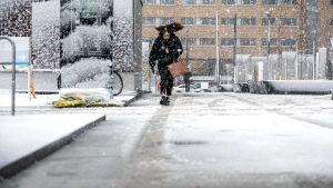Kvinna som går i snöfall.