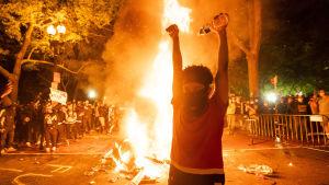 Demonstrant framför eld.