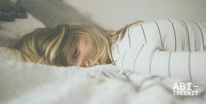 Väsynyt nainen makaa sängyllä.