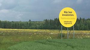 en rund och gul skylt på en äng. på skylten står det här bor kvaliteten.